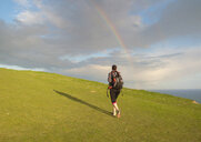 Young female hiker, hiking up hill toward rainbow - CUF34727