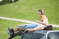 Mid adult couple relaxing on car roof - CUF34739