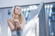 Mid adult woman with takeaway coffee sitting on stairway - CUF34763