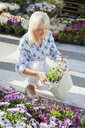 Woman with bag of flowers at market, Mallorca, Spain - CUF34778