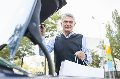 Senior adult businessman putting bag in car boot - CUF34793