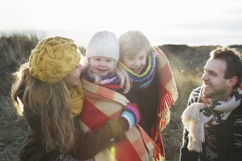 Mid adult couple in sand dunes with their son and daughter wrapped in blanket - CUF34811