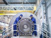 Engineers repairing steam turbine in workshop - CUF34964