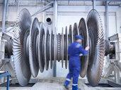 Engineer inspecting steam turbine blades in repair bay of workshop - CUF34967