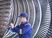 Engineer inspecting repair to steam turbine blade in workshop - CUF34970