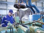 Engineer operating machinery in steam turbine repair workshop - CUF34976