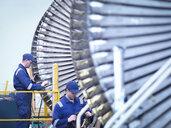 Engineers repairing steam turbine in repair bay in workshop - CUF34979