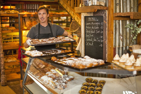 Mature man holding tray of fresh pastries - CUF35003