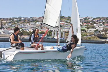 Three young friends sailing in harbor - CUF35009