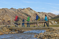 Family crossing the river bridge at  Landmannalaugar, Fjallabak, Iceland - CUF35243