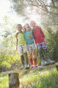 Three children standing on garden seat with arms around each other - CUF35258