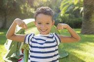 Portrait of boy in garden flexing muscles - CUF35264