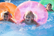 Three children swimming with inflatable rings in garden swimming pool - CUF35270
