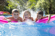 Portrait of three children splashing on inflatable mattress in garden swimming pool - CUF35273