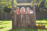Portrait of three girls selling lemonade at stand in park - CUF35333