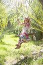 Girl sitting swinging on tree swing in garden - CUF35339