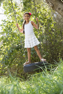 Girl standing swinging on tree tire swing in garden - CUF35342