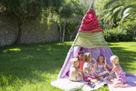 Five girls playing clapping games in front of teepee - CUF35351