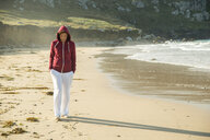 Mature woman strolling on beach with hands in pockets, Camaret-sur-mer, Brittany, France - CUF35369