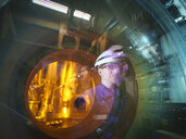Engineer reflected in glass of fuel rod handling machine in nuclear power station - CUF35528