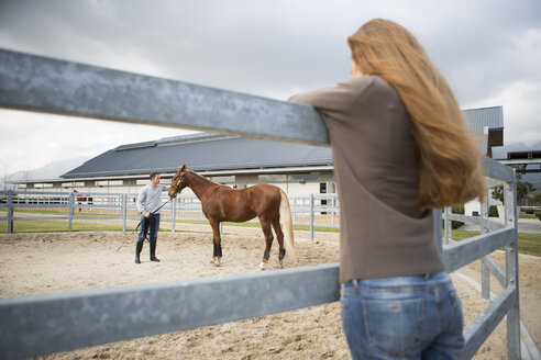 Young woman watching stablehand train horse in paddock ring - CUF35756