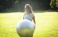 Mid adult woman holding up exercise ball in field - CUF35789