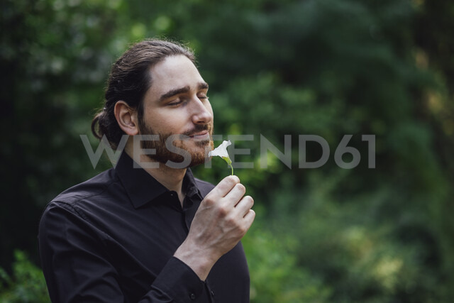 Young man, dressed in black, standing in park, smelling flower - JSCF00101