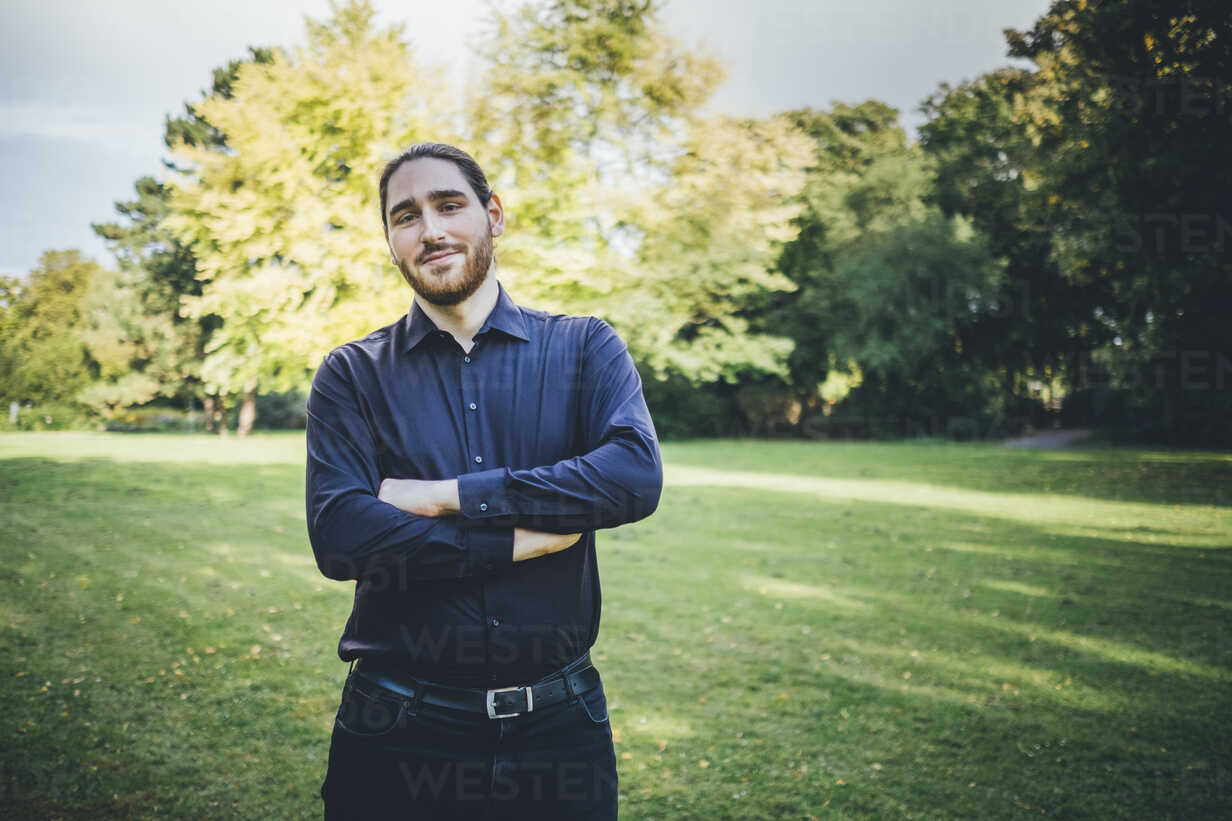Young businessman standing in park with arms crossed - JSCF00104 - Jonathan Schöps/Westend61