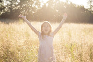 Young girl standing in field at summer evening - LVF07161