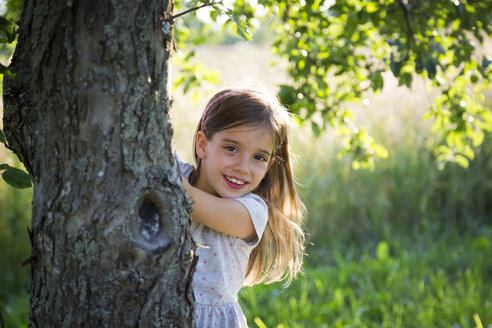 Young girl behind tree trunk at summer evening - LVF07164