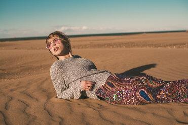 Spain, fashionable young woman wearing sunglasses lying on the beach - ACPF00052