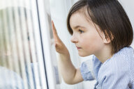 Young girl looking out of window - CUF35962