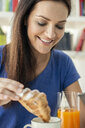 Close up of young woman dipping croissant in coffee cup - CUF35977