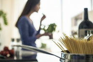Blurred image of young woman preparing food in kitchen - CUF35980