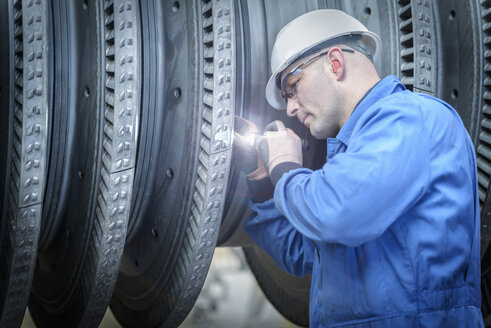 Engineer with torch inspecting turbine during power station outage - CUF36082