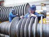 Engineers inspecting turbine during power station outage, portrait - CUF36100