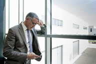 Businessman using smartphone by glass wall - CUF36121
