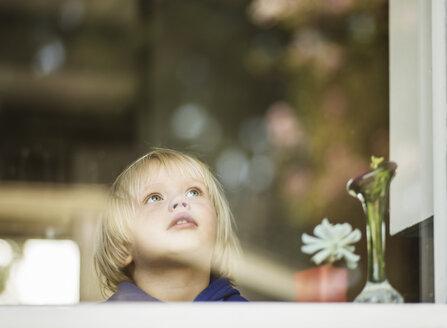 Young boy at house window gazing upward - CUF36145