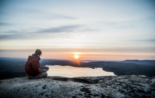 Young female hiker gazing at sunset over distant lake - CUF36262