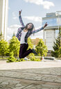 Young woman jumping mid air in city - CUF36265