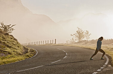 Female runner warming up on roadside, Capel Curig, Snowdonia, North Wales, UK - CUF36307