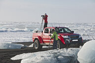 Photographer on top of off road vehicle on iceberg beach, Jokulsarlon, South East Iceland, Iceland - CUF36310