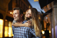 Couple giving piggy back on city street at night - CUF36316