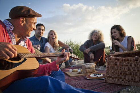 Five adult friends picnicing on Bournemouth beach, Dorset, UK - CUF36349