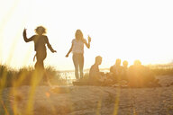 Six adult friends partying at sunset on Bournemouth beach, Dorset, UK - CUF36352