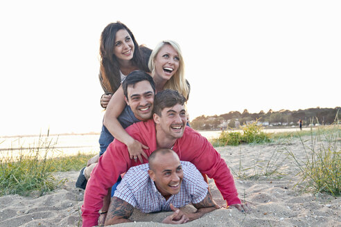 Group of friends making human pile on beach - CUF36367