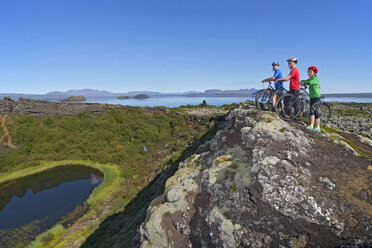 Cyclists looking out into a craterlake at Thingvellir national park with Thingvallavatn and Langjokull in the background, Nesjavellir, Iceland - CUF36433
