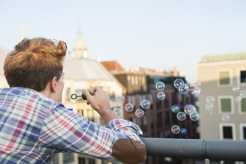 Young man on rooftop, blowing bubbles, rear view - CUF36481