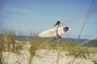 Woman with surfboard on beach, Lacanau, France - CUF36502