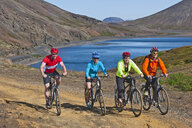 Cyclists cycling up track, Kleifarvatn in background, Reykjanes, South West Iceland - CUF36508